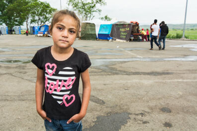 <p><strong>Girl at an informal refugee camp behind a roadside petrol station</strong><br />Northern Greece 2016</p>